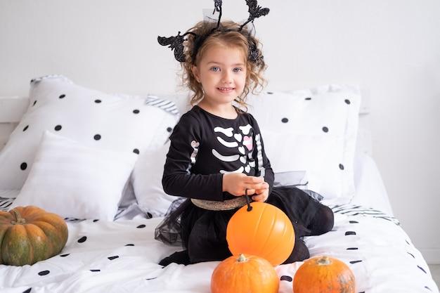 Linda garota com fantasia de bruxa segurando a lanterna de abóbora em um quarto decorado
