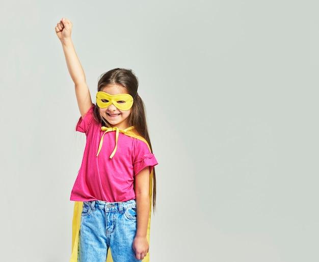 Linda garota com fantasia de super-herói com a mão levantada