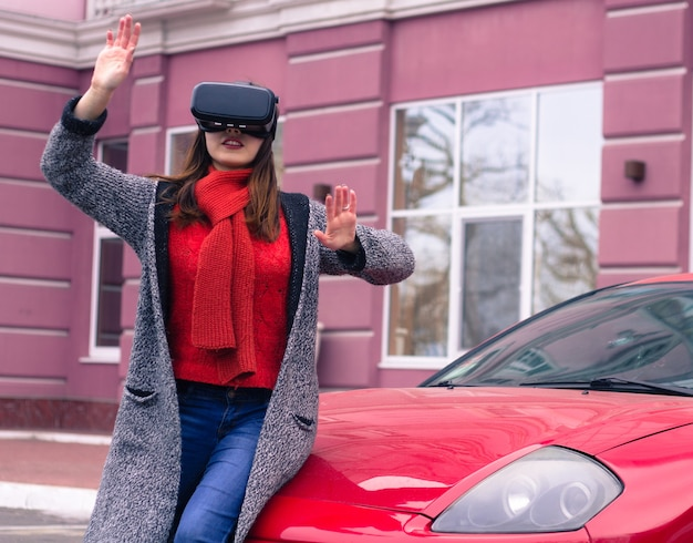 Linda garota com fone de ouvido de realidade virtual vr em carro esporte vermelho na rua