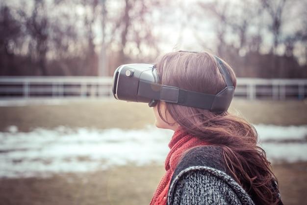 Linda garota com fone de ouvido de realidade virtual vr na rua interessada em imagem 360
