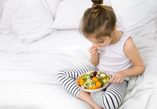 Linda garota com frutas e legumes no espaço da cópia de cama branca.