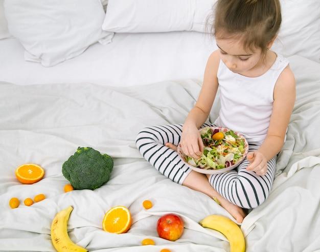 Linda garota com frutas e legumes no fundo de um espaço de cópia de cama branca.