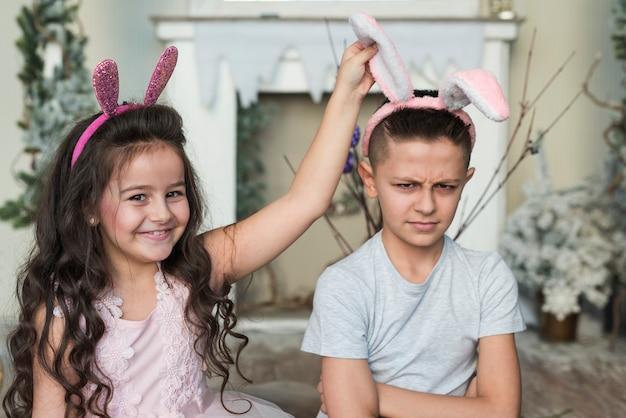 Linda garota com garoto ofendido em orelhas de coelho