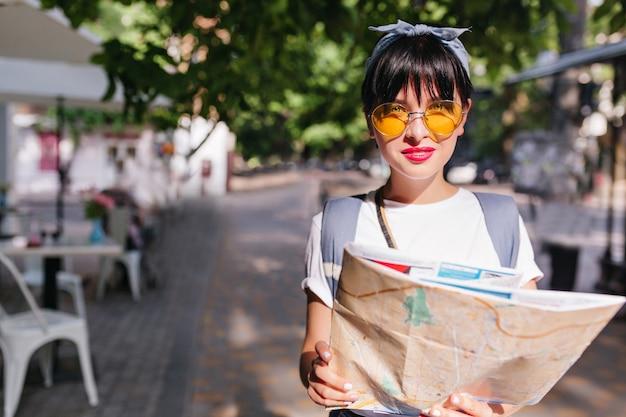 Linda garota com grandes olhos azuis olhando através de elegantes óculos de sol amarelos enquanto caminha por um café ao ar livre com uma mochila