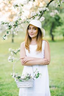 Linda garota com grandes olhos brilhantes e um sorriso doce e um chapéu está segurando uma cesta de vime branca