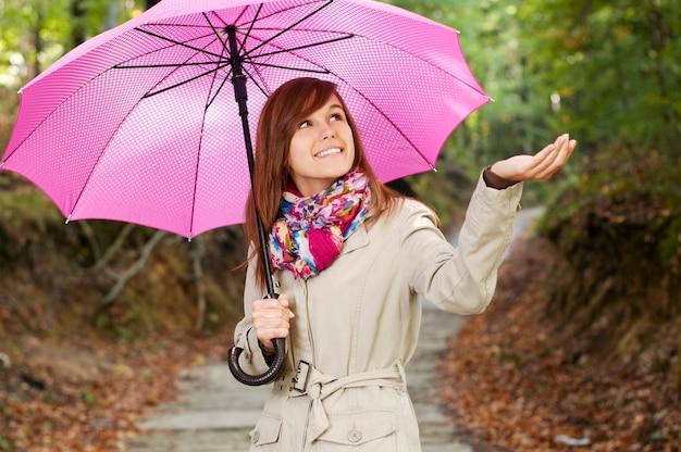 Linda garota com guarda-chuva checando