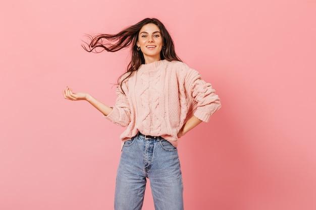 Linda garota com humor brincalhão, posando em fundo rosa. jovem morena com suéter tricotado brinca de cabelo.