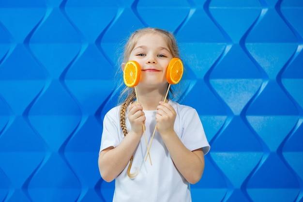 Linda garota com laranjas, ela as come em um fundo azul