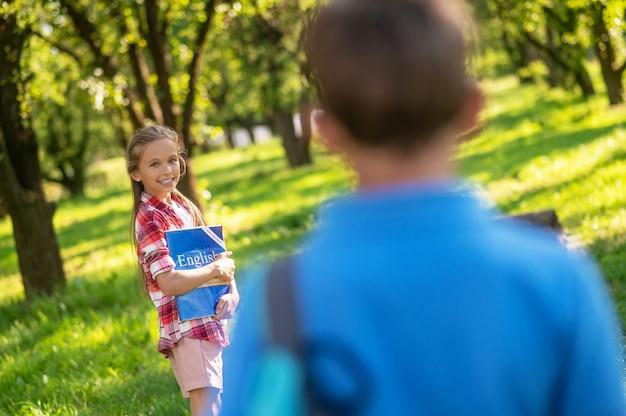 Linda garota com livro e menino de volta para a câmera
