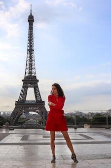 Linda garota com longos cabelos castanhos com vestido vermelho fica na frente da torre eiffel