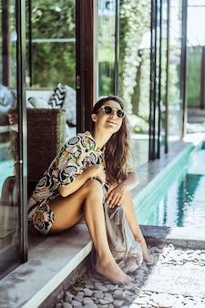Linda garota com longos cabelos castanhos em óculos de sol em uma linda casa, refletida em óculos