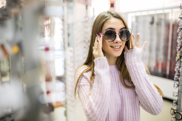 Linda garota com longos cabelos dourados e aparência bonita demonstra a diferença dos óculos em loja profissional