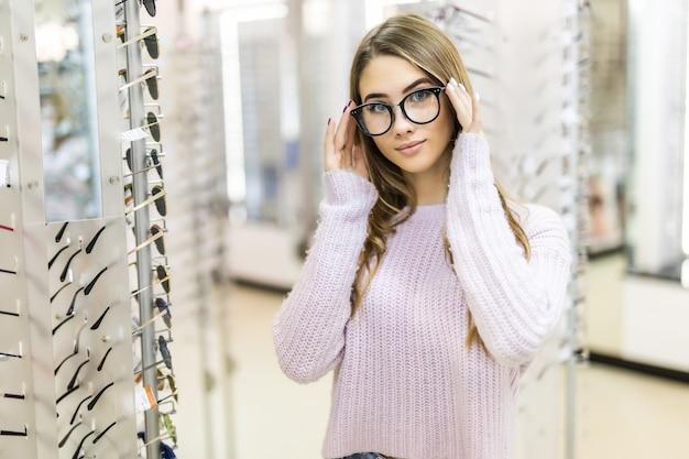 Linda garota com longos cabelos dourados e aparência de modelo demonstra a diferença dos óculos em loja profissional