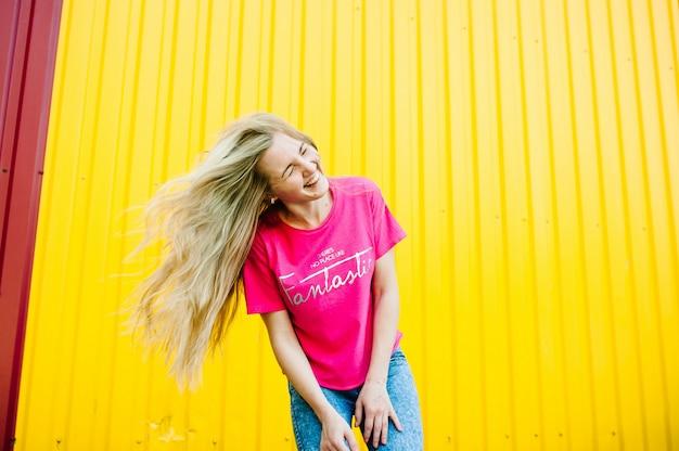 Linda garota com longos cabelos loiros na camisa rosa e calça jeans azul.