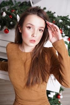 Linda garota com longos cabelos loiros perto de um piano de cauda branco com decoração de natal
