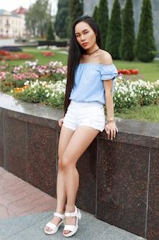 Linda garota com longos cabelos negros em uma blusa de verão e shorts brancos perto das flores