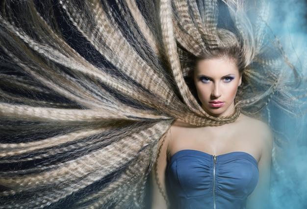 Linda garota com longos cabelos ondulados balançando na fumaça está no fone.portret azul.
