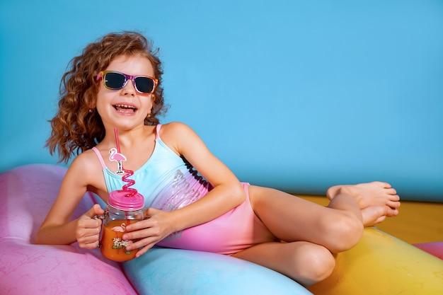 Linda garota com maiô colorido e óculos escuros segurando pinea