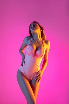 Linda garota com maiô elegante isolado no fundo do estúdio gradiente em luz de néon.