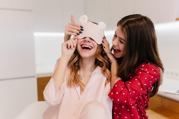 Linda garota com manicure preta, brincando com a irmã de manhã. modelo feminino encaracolado engraçado na máscara de dormir rosa relaxante com o melhor amigo.