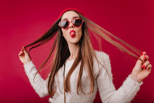 Linda garota com manicure vermelha brincando com seu cabelo escuro