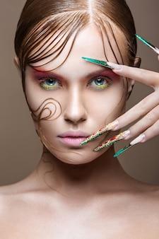 Linda garota com maquiagem brilhante, penteado criativo, unhas compridas.