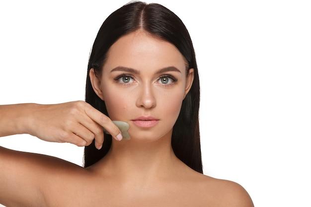 Linda garota com maquiagem natural e pele limpa. segura na mão um limpador de rosto de jade para emagrecer rugas anti-envelhecimento