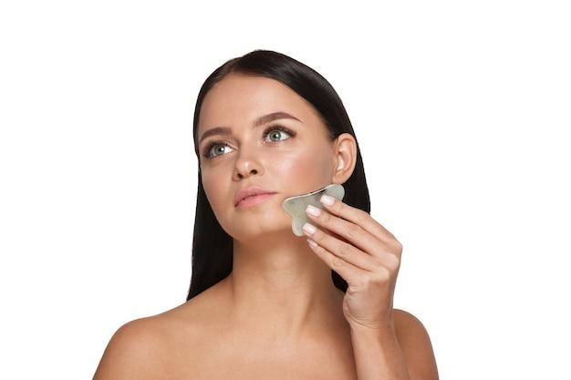 Linda garota com maquiagem natural e pele limpa. segura na mão um limpador de rosto de jade