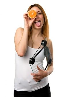 Linda garota com máquina de pesagem, segurando uma laranja