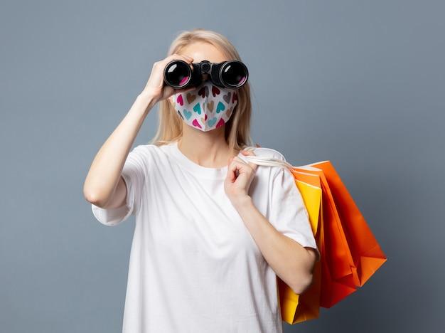 Linda garota com máscara facial com sacolas de compras e binóculos no espaço cinza