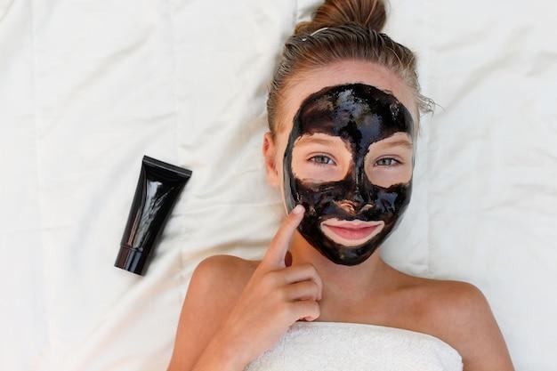 Linda garota com máscara facial de argila preta.