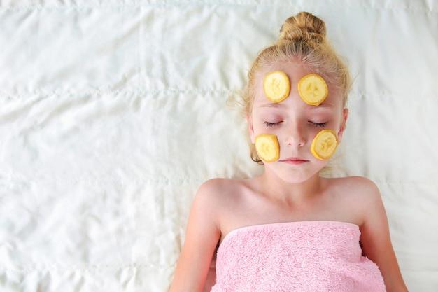 Linda garota com máscara facial de bananas. vista do topo. postura plana.