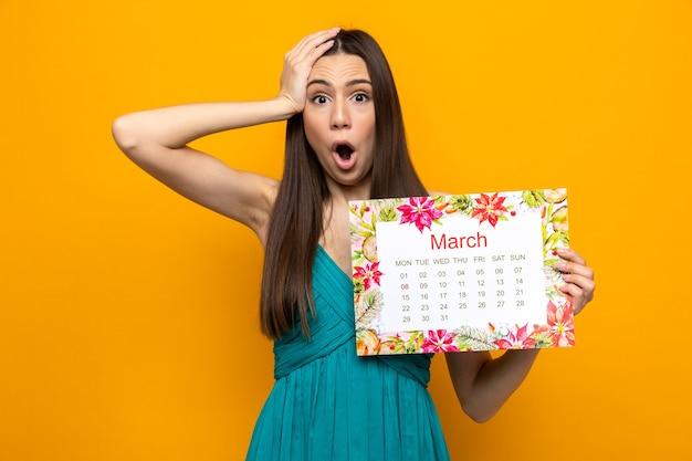 Linda garota com medo de colocar a mão na cabeça no feliz dia da mulher segurando o calendário
