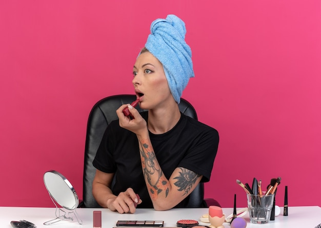 Linda garota com medo de olhar para o lado sentado à mesa com ferramentas de maquiagem enroladas em uma toalha no cabelo, aplicando batom isolado no fundo rosa