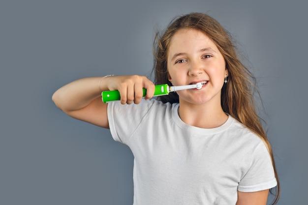 Linda garota com o cabelo solto em pé, escovando os dentes com uma escova elétrica, isolada em um fundo cinza
