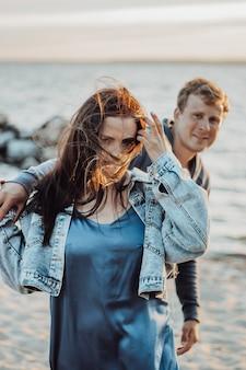 Linda garota com o namorado caminha na praia. cabelo comprido esvoaçando ao vento.