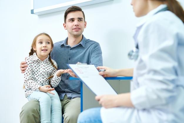 Linda garota com o pai em visita ao médico