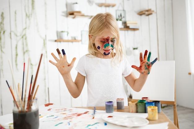 Linda garota com o rosto pintado, vestindo camiseta branca, desenho com as mãos em folhas de papel brancas