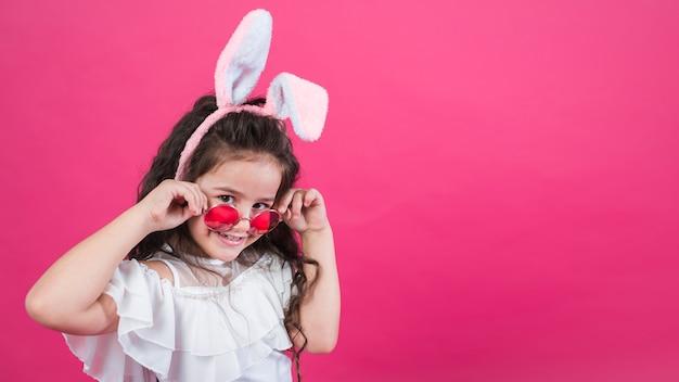 Linda garota com orelhas de coelho, ajustando os óculos de sol