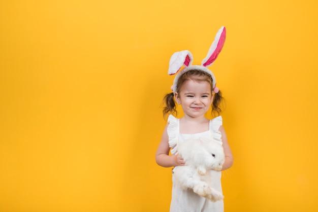Linda garota com orelhas de coelho em pé com coelho