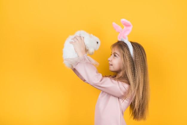 Linda garota com orelhas de coelho olhando coelho
