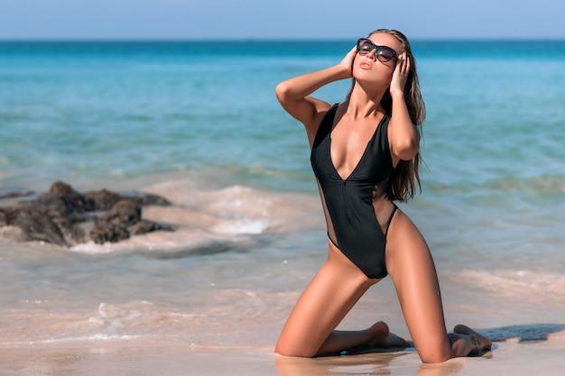 Linda garota com os lábios carnudos posando enquanto está sentado à beira-mar