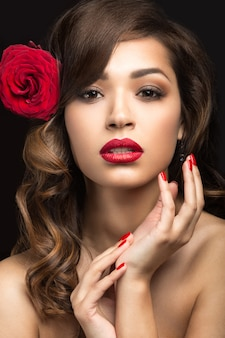 Linda garota com os lábios vermelhos e uma rosa no cabelo.