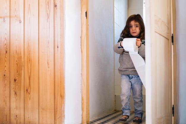 Linda garota com papel higiênico, olhando para a câmera