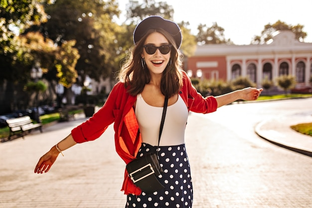 Linda garota com pele clara, cabelo escuro, boina francesa, óculos de sol com saia de bolinhas, blusa branca e camisa vermelha andando pela cidade ensolarada e rindo