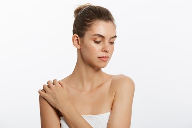Linda garota com pele lisa sobre um fundo claro com maquiagem natural