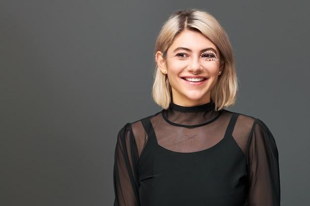 Linda garota com penteado bob tingido, maquiagem artística e piercing no nariz usando um vestido transparente sobre a parte superior de alça preta, posando contra uma parede em branco com espaço de cópia para sua informação