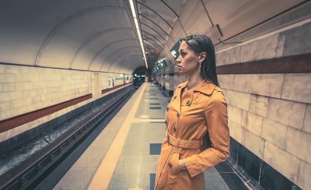 Linda garota com pernas longas e lindas em um casaco amarelo primavera e uma bolsa branca no metrô