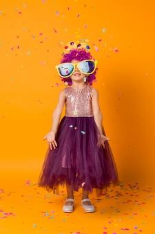 Linda garota com peruca de palhaço e confete