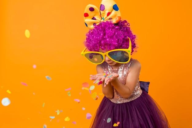 Linda garota com peruca de palhaço soprando confete